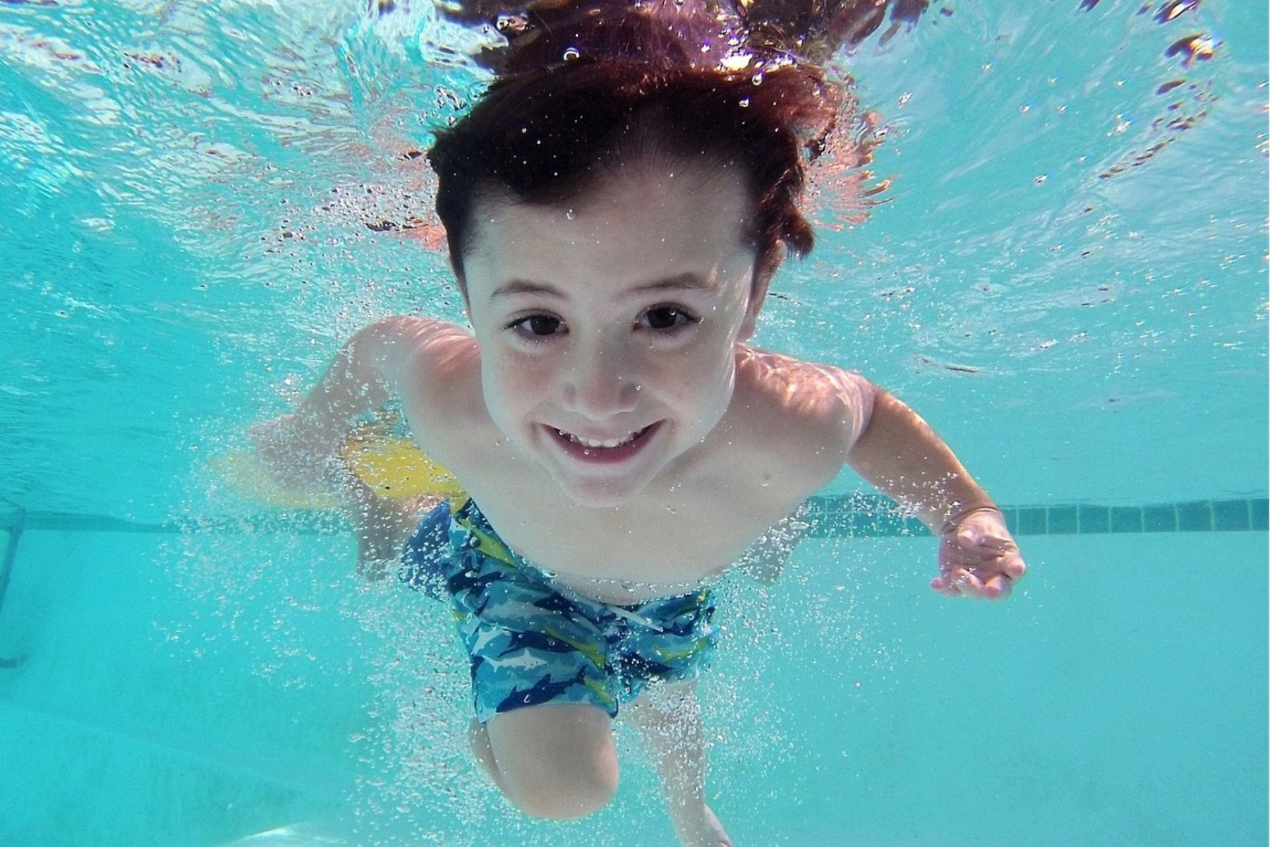 Boy swimming underwater with eyes open