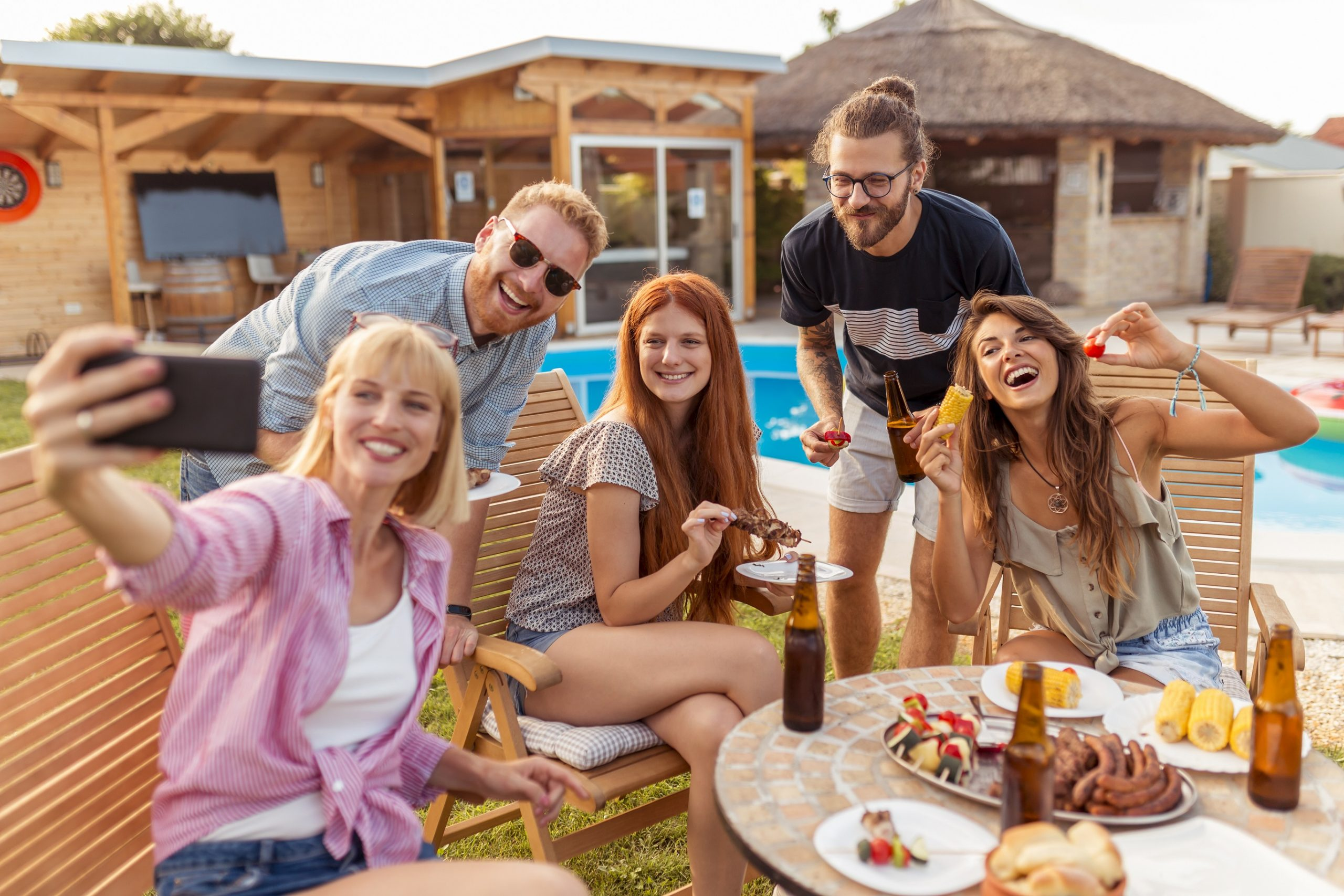 Friends taking a selfie at backyard barbecue party