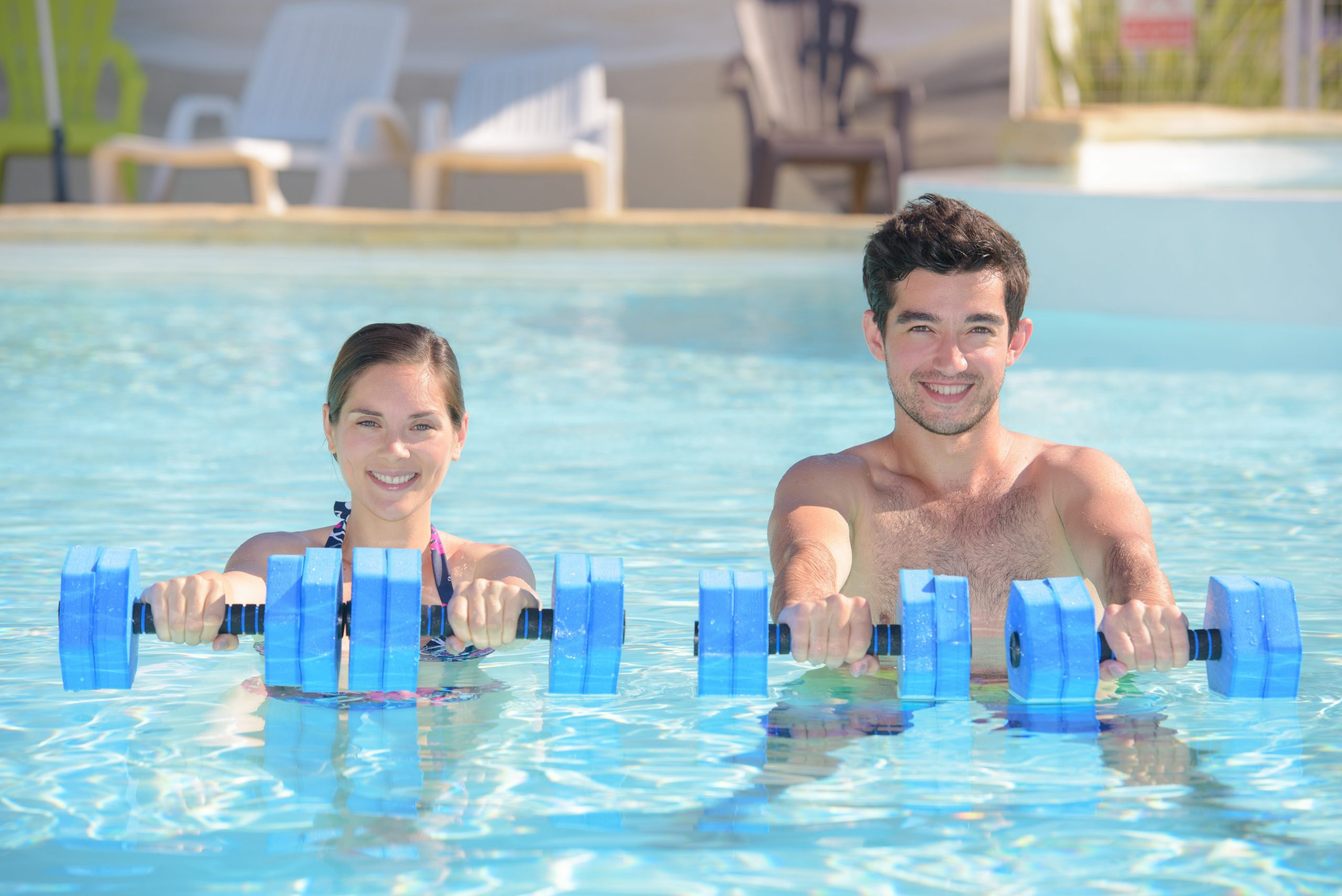 A couple using water weights in an outdoor pool